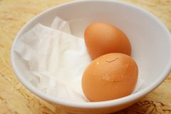 Broken eggs in white bowl on wooden background. Stock Images