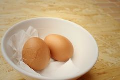 Broken eggs in white bowl on wooden background. Royalty Free Stock Photography