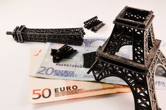 Broken Eiffel tower on money Stock Photo
