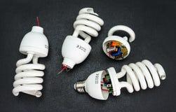 Broken energy saving light bulb, isolated on a black background. stock photography