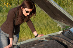 Broken engine. Woman looking in the broken engine Royalty Free Stock Photography