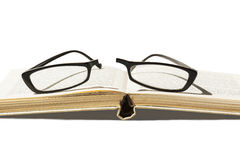 Broken eyeglasses and open book. Broken eyeglasses laying on an open book, on white background, isolated, with clipping path Royalty Free Stock Photo