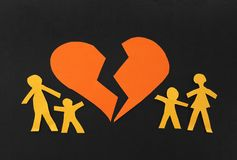Broken family. Paper family split apart with broken heart in the middle Royalty Free Stock Images