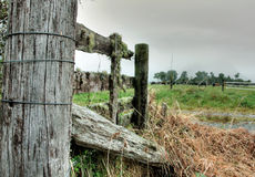 Broken Fence. An old broken fence on farmland Stock Photo