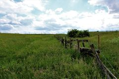 Broken fence with horizon. Broken fence with barbed wire in a field with a horizon Royalty Free Stock Photography