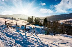 Broken fence on a snowy slope in rural are. Lovely winter landscape with bright sun over the mountain ridge Royalty Free Stock Images