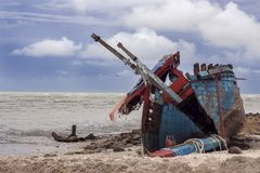 Broken fishing boat wreckage on a sandy beach under bad weather Royalty Free Stock Images