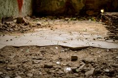 Broken floor with cracked tiles in lost abandonend building. Broken floor tiles in lost abandonend building Royalty Free Stock Image