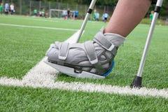 Broken foot, crutches - sports injury Stock Photos