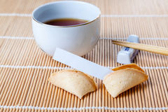 Broken Fortune Cookie with Slip and Chopsticks and Tea. Broken fortune cookie with blank slip on bamboo mat with Chinese chopsticks and tea in Chinese cup stock photography