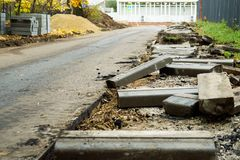 Broken freshly dug up old curbstones with pieces of an asphalt and earth lying on the road in Moscow. Road curb replacement on the Moscow street in Autumn royalty free stock photo