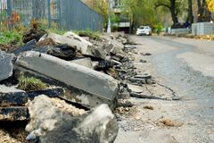 Broken freshly dug up old curbstones with pieces of an asphalt and earth lying on the road in Moscow. Road curb replacement on the Moscow street in Autumn stock photo