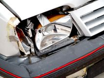 Broken front headlight on white car Royalty Free Stock Photo