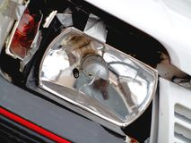 Broken front headlight on white car Stock Photography