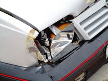 Broken front headlight on white car Royalty Free Stock Image