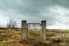 Broken gate on a field with barb wire Royalty Free Stock Photos