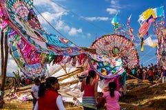 Broken giant kite, All Saints' Day, Guatemala. Santiago Sacatepequez, Guatemala - November 1, 2010: Broken giant kite among graves & upright giant kites. Locals Royalty Free Stock Image