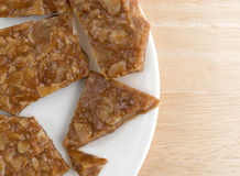 Broken ginger brittle on a plate atop wood table Stock Photos