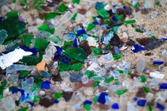 Broken glass bottles on white sand. Bottles is green and blue colour. Trash on the sand. Ecological problem royalty free stock photography