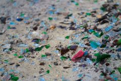 Broken glass bottles on white sand. Bottles is green and blue colour. Trash on the sand. Ecological problem stock photo