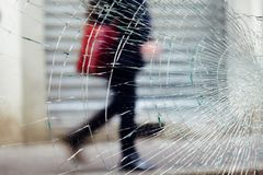 Broken glass in the city centre. Florence,Italy - circa January 2016 - Moving woman subject pass between a broken glass and a city centre shop going shopping stock photography