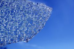 Broken glass cracked over blue background Royalty Free Stock Photos