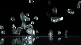 Broken glass falls to the floor. Black background. Slow motion. Broken glass falls to the floor and hit it spreading around. Black background. Slow motion