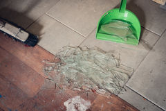 Broken glass on the floor. Broken window glass on the floor with brush and dustpan. Tiding up concept Stock Image