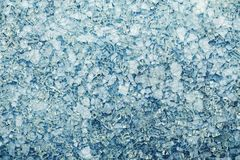 Broken glass fragments on a blue background. Background of broken glass fragments. View from above. stock images