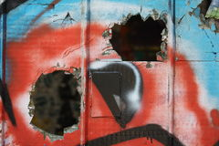 Broken glass with graffiti. Close up view of an old damaged glass wall with colorful graffiti royalty free stock photo