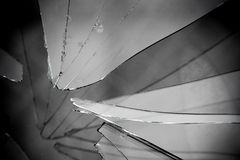 Broken Glass Grayscale. Sharp glass hole cracks splinters, broken glass by the street, grayscale background Stock Photo