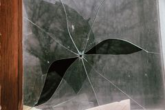 Broken glass with hole from bullet Stock Photo