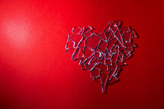 Broken glass heart on red background royalty free stock image