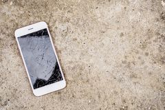 Broken glass of mobile phone screen. On concrete floor background stock image