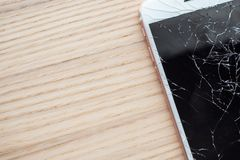 Broken glass of mobile phone screen. On wooden background stock photography