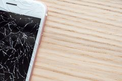 Broken glass of mobile phone screen. On wooden background royalty free stock images