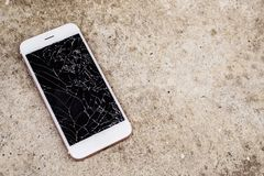 Broken glass of mobile phone screen on concrete floor. Background royalty free stock photo