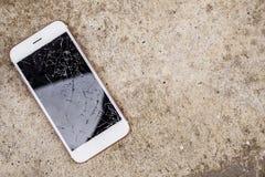 Broken glass of mobile phone screen on concrete floor. Background stock photo