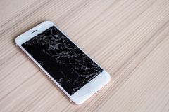 Broken glass of mobile phone screen on wood background. Broken glass of mobile phone screen on wooden background royalty free stock image