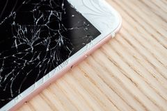 Broken glass of mobile phone screen on wood background. Broken glass of mobile phone screen on wooden background stock photography