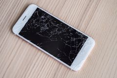 Broken glass of mobile phone screen on wood background. Broken glass of mobile phone screen on wooden background stock photo