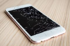 Broken glass of mobile phone screen on wood background. Broken glass of mobile phone screen on wooden background royalty free stock photos