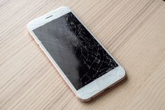 Broken glass of mobile phone screen on wood background. Broken glass of mobile phone screen on wooden background royalty free stock images