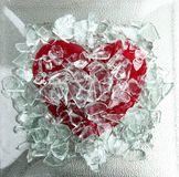 Broken glass red heart. Broken glass red candy sweet heart in a plate, metaphor stock photo