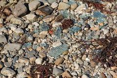 Broken glass on rocky coastline Stock Photos