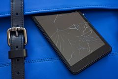 Broken glass of smart phone on the blue. Leather bag royalty free stock images