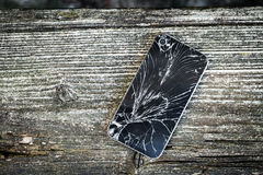 Broken glass of smart phone. On the grunge wood. Copy space. Selective focus. Low depth of field royalty free stock image