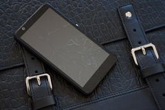 Broken glass of smart phone on leather bag. Broken glass of smart phone on the black leather bag stock images
