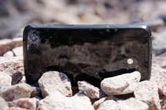 Broken glass of smartphone on gravel granite stones. Selective focus. Broken glass of smartphone on granite stones. Selective focus royalty free stock photo