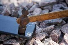Broken glass of smartphone with hammer on gravel stones. Selective focus.  stock photography